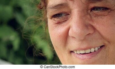 Happy woman of middle age has a rest in park on a swing -...