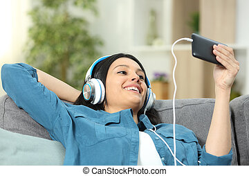 Happy woman on a couch watching videos on phone