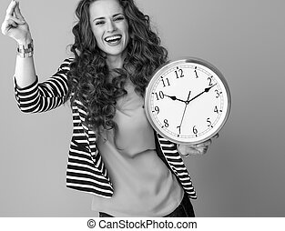 happy woman on background with clock snapping fingers