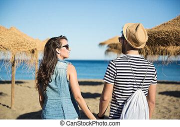 Happy woman on beach holding her boyfriend by hand