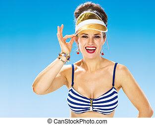 happy woman on beach straightening yellow sun visor - ...