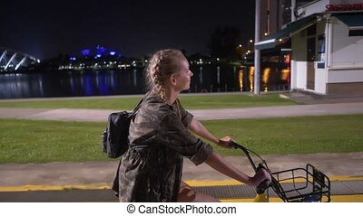 Happy woman on her bicycle at night