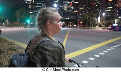 Happy woman on her bicycle at night - Attractive happy woman...