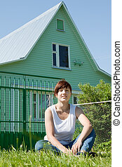 Happy woman on lawn in front of home