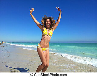 Happy woman on Miami beach. - Woman running on Miami beach....
