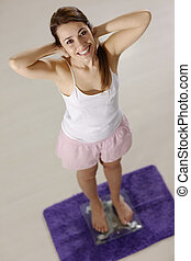 happy woman on scales satisfied for weight loss