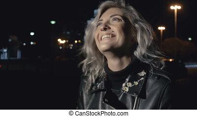 Happy woman on street at night