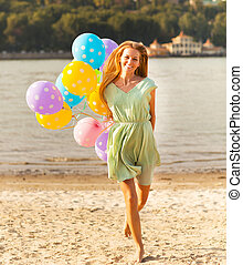 Happy woman on the beach with colored polka dots balloons