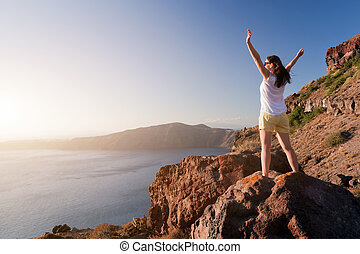Happy woman on the rock with hands up. Santorini island, Greece