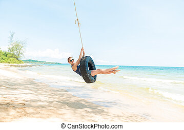 Happy woman having fun on tire swing at the beach. Phu Quoc, Vietnam