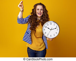 happy woman on yellow background with clock snapping fingers