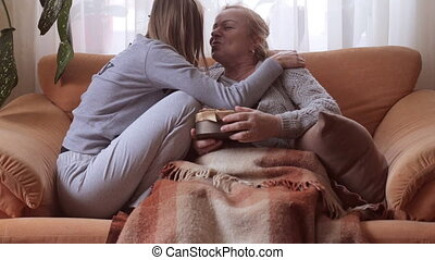 Happy woman opens a gift from her granddaughter and kisses her granddaughter