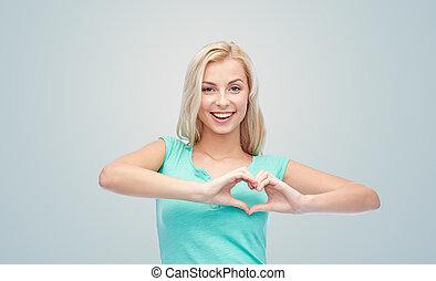 happy woman or teen girl showing heart shape sigh