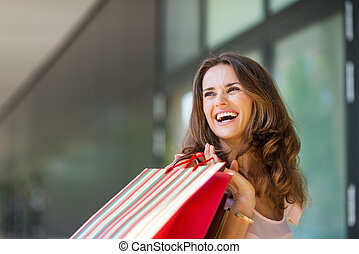 Happy woman out shopping, holding up colourful shopping bags...