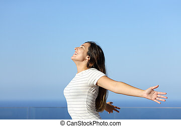 Happy woman outstreching arms in a balcony on the beach