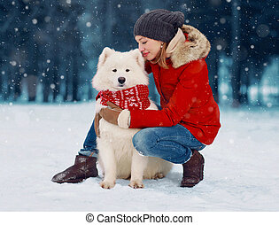 Happy woman owner petting embracing white Samoyed dog outdoors wearing red scarf while sitting on snow in winter snowy day over flying snowflakes