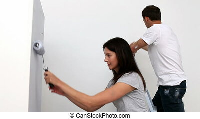 Happy woman painting a wall