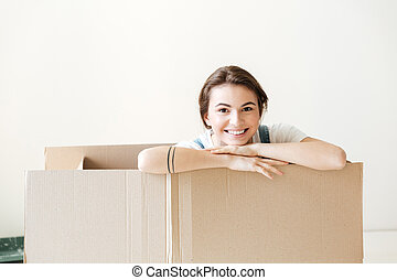 Happy woman peeking out from box