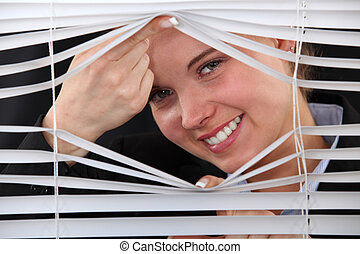 Happy woman peering through blinds