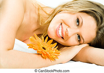 Photo of young pretty woman lying in the spa salon and enjoying aromatherapy with a flower near by