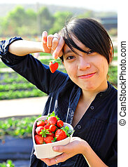 happy woman pick strawberry