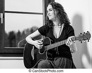 Happy woman playing acoustic guitar