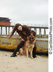 Happy woman playing with her German shepherd dog