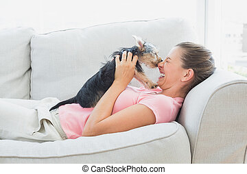 Happy woman playing with her yorkshire terrier on the couch...
