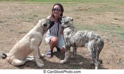 Happy woman  playing with two huge dogs