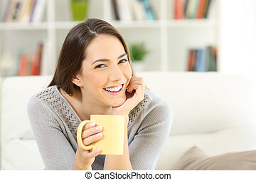 Happy woman posing holding a coffee cup