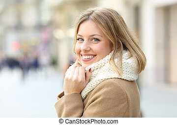Happy woman posing looking at camera in winter in the street