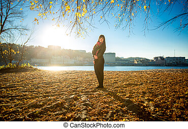 woman posing on sandy river beach at sunny autumn day