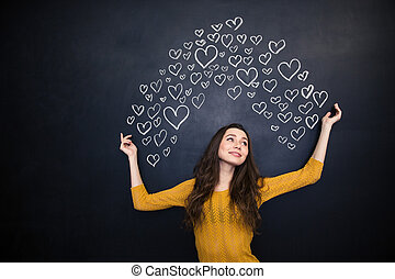 Happy woman posing over black board with drawn hearts -...