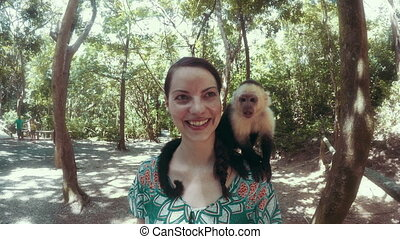 Happy woman posing with a monkey on her shoulders