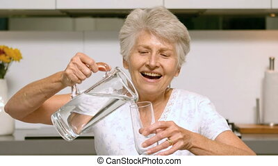 Happy woman pouring glass of water
