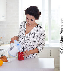 Happy woman preparing a cup of coffee wearing pajamas