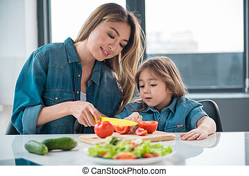 Happy woman preparing salad for her daughter