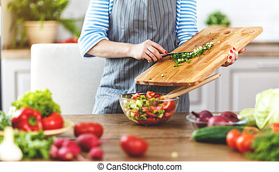happy woman preparing vegetable salad in the kitchen