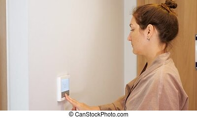 pretty woman in beige bathrobe presses keys of climate control panel on wall close up