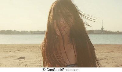 Happy woman put tongue out and shaking her head with long disheveled hairs