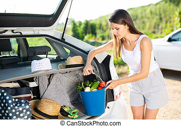 Happy woman puts basket with ripe vegetables in car