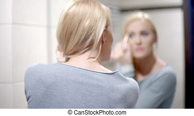 Happy Woman Putting Make on in Front of Mirror
