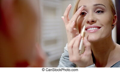 Happy Woman Putting Make up in Front a Mirror