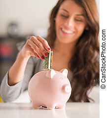 Happy Woman Putting Note In Piggy Bank