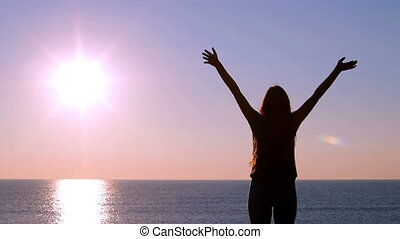 Happy woman raising arms at sunrise - Back view of a happy...