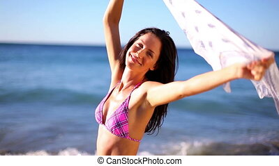 Happy woman raising her sarong on the beach