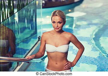 happy woman raising upstairs in swimming pool