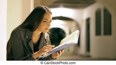 Happy woman reading a book in the night