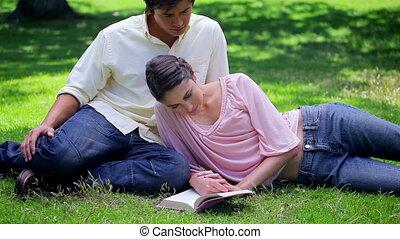 Happy woman reading a book near her boyfriend