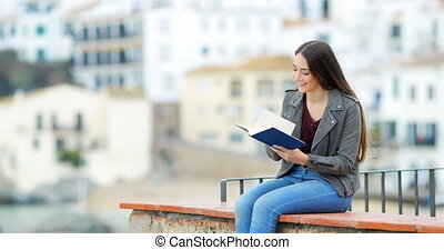 Happy woman reading a book on a ledge